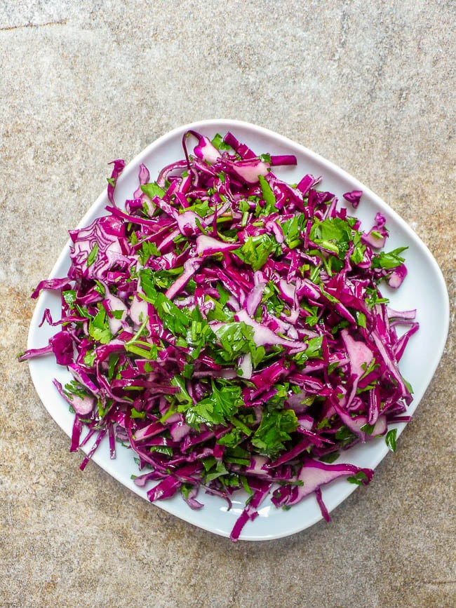 Red cabbage salad on white plate, top down