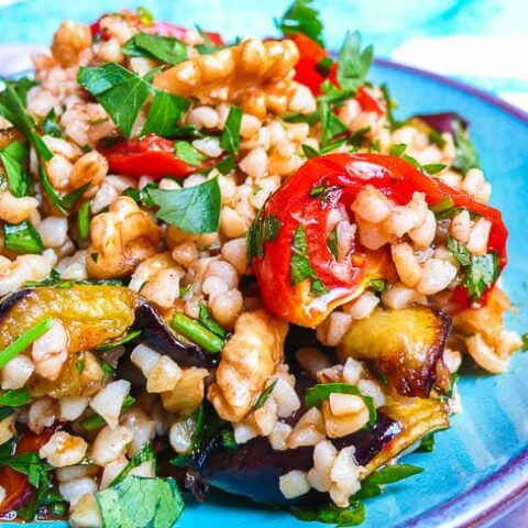 Bulgur salad with tomato and aubergine in turquoise dish seen from side
