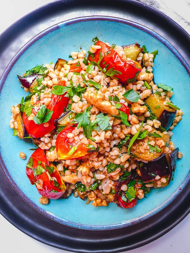 Bulgur salad with tomato and aubergine in turquoise dish seen from above