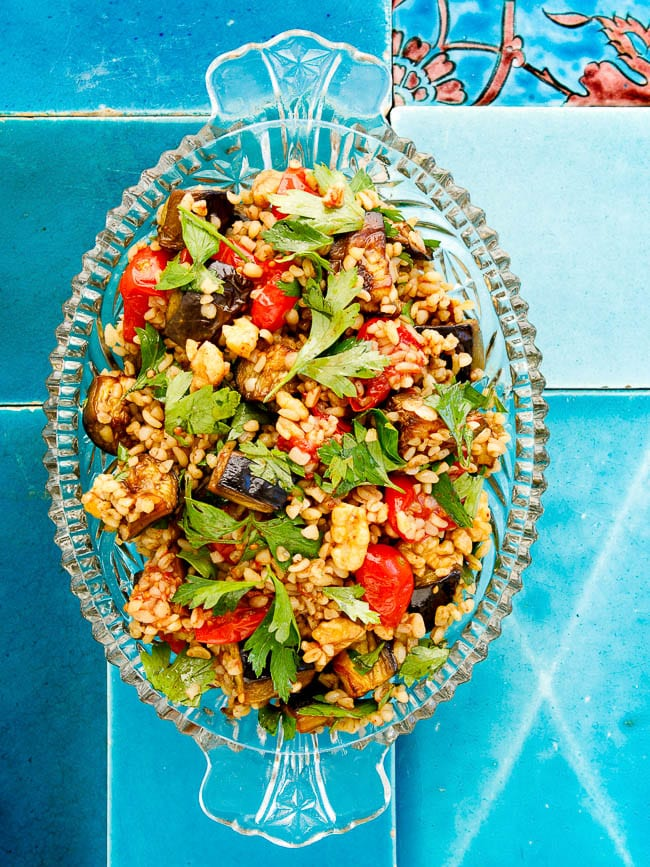 Bulgur salad with tomato and aubergine in transparent dish on turqoise tiles seen from above