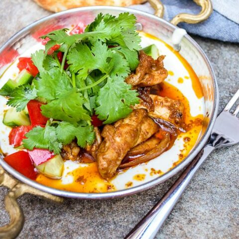Shawarma spiced chicken with tahini yoghurt in traditional saucepan seen from eye level
