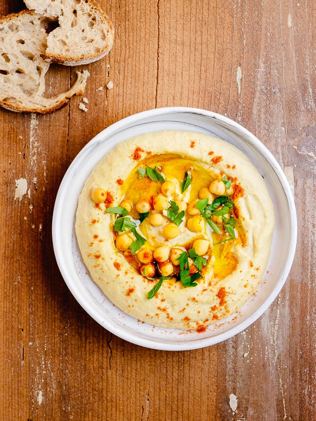 Hummus tehina on a plate with wooden backdrop