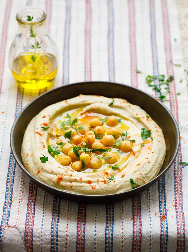 Hummus tehina from the side on beautiful, old textile