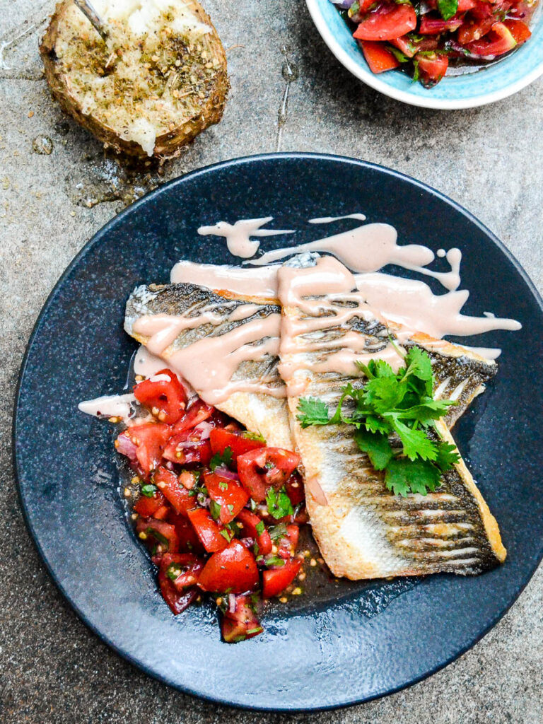 Pan fried sea bass with tahini sauce and tomato salad seen from above