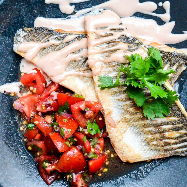 Pan fried sea bass with tahini sauce and tomato salad seen up close