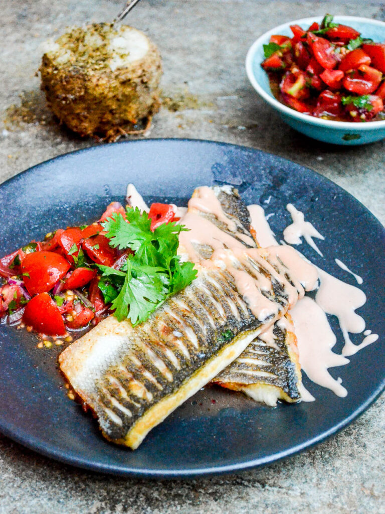 Pan fried sea bass with tahini sauce and tomato salad seen from the side
