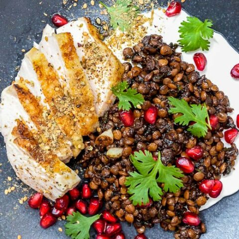 Chicken with Syrian lentils and labneh on a black plate, seen from above