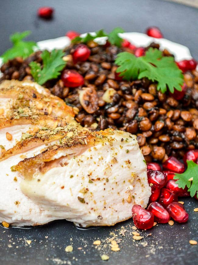 Chicken with Syrian lentils and labneh on a black plate, seen up close with chicken in focus
