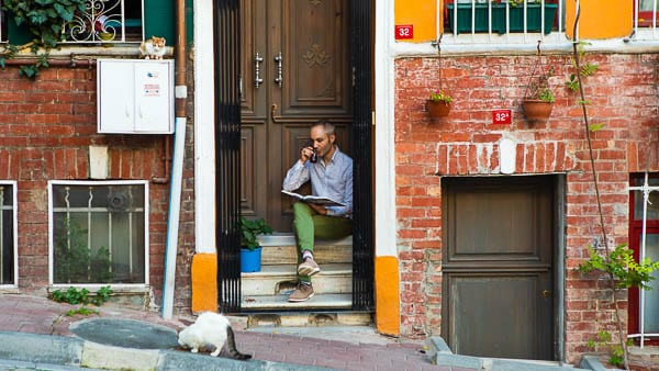 Vidar Bergum sitting on front porch in front of his house, reading a book and drinking tea with a street cat eating in front