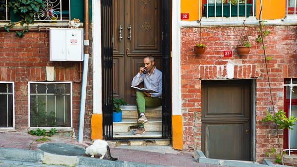 Vidar Bergum on the front porch of his home, drinking tea, with a street cat eating something on the street in front of him