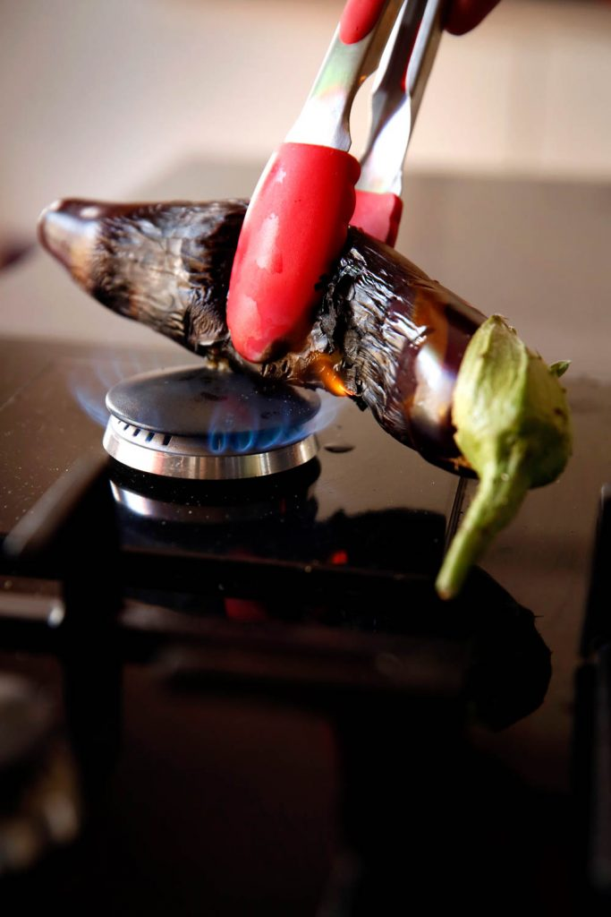 Burning aubergine held by tongs over a gas flame