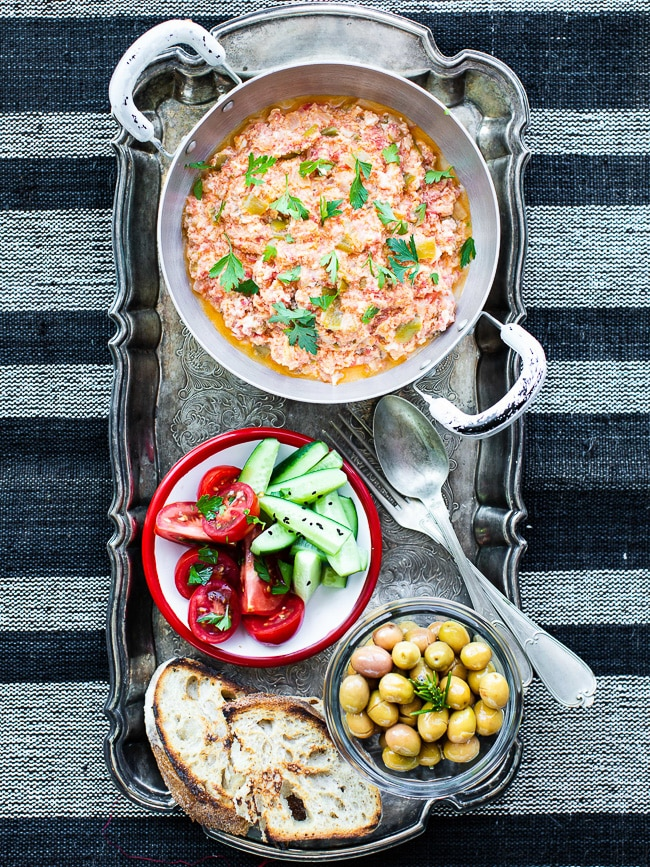 Menemen in pan on tray with vegetables, olives & bread