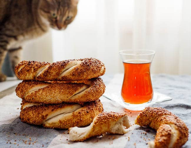 Stacked simit with tea and cat in background