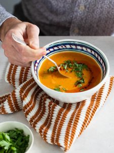 Turkish red lentil soup being eaten, seen from side