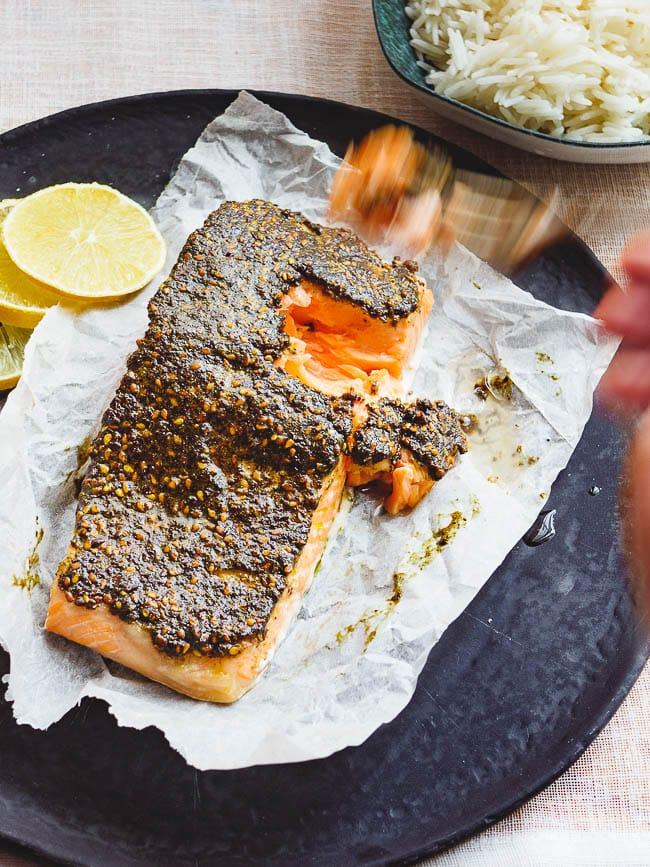 Fork lifting a piece of za'atar baked salmon