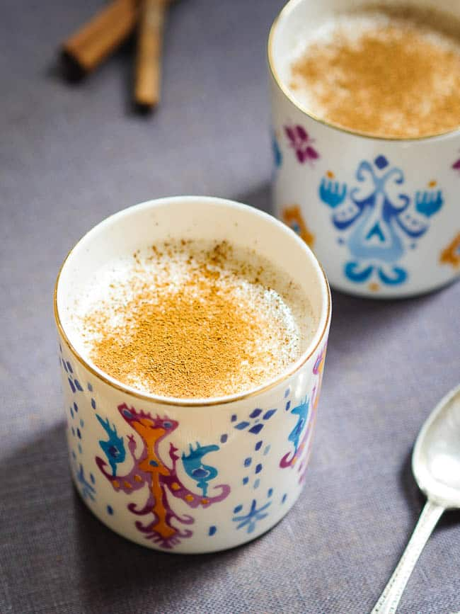 Salep in two colourful cups with sprinkling of cinnamon seen from eye-level