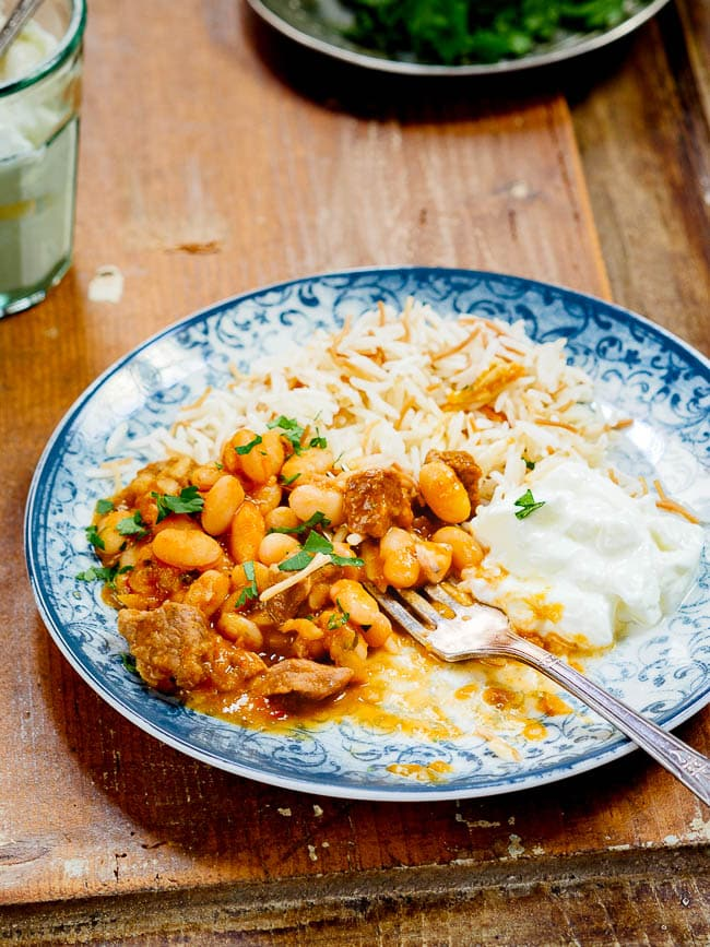 Turkish white bean stew with rice and yoghurt on a patterned blue plate, half eaten