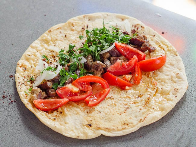 Lavash bread topped with meat, tomato, onion and parsley, seen from eye level