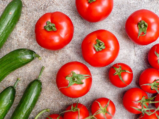 Fresh tomato and cucumber on stone background, seen from above