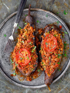 Two Turkish stuffed aubergine on old metal tray, seen from above