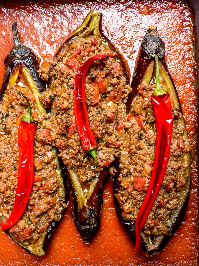 Three karniyarik in oven tray with tomato sauce around, before cooking